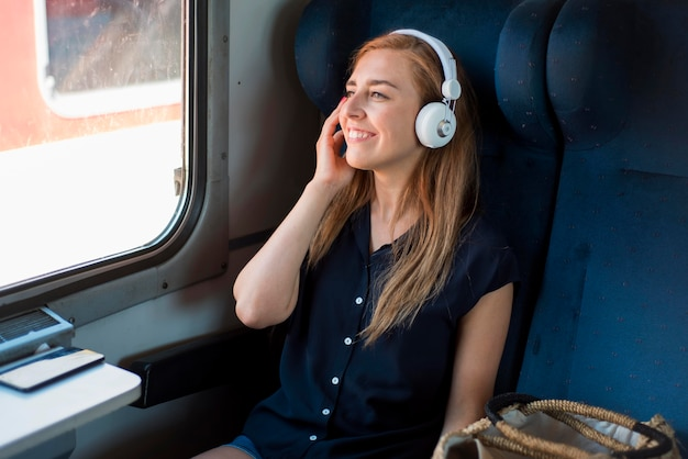 Mid shot woman sitting in train listening to music