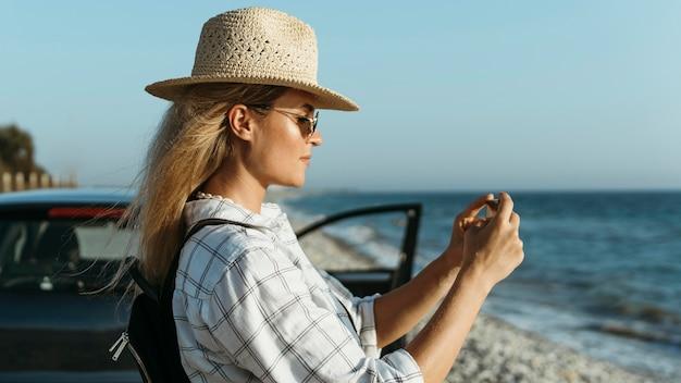 車で海の写真を撮るミディアムショットの女性