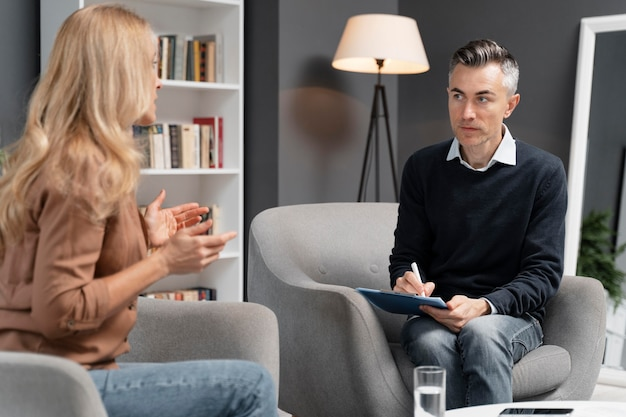 Mid shot woman talking to man therapist