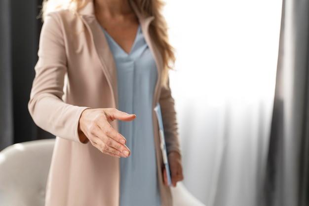 ミディアムショットの女性セラピストが手を差し伸べる