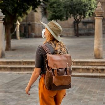 Donna a metà colpo che cammina attraverso la città che indossa la maschera