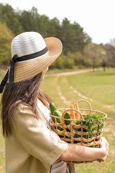 Mid shot woman wearing hat and holding basket with groceries