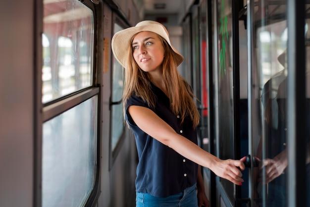 電車の中で帽子をかぶっている半ばショット女性
