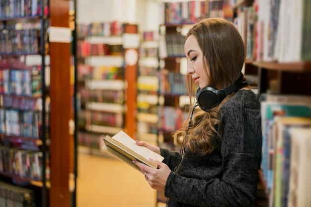 Середина выстрела женщина носить наушники на шее, читая book0