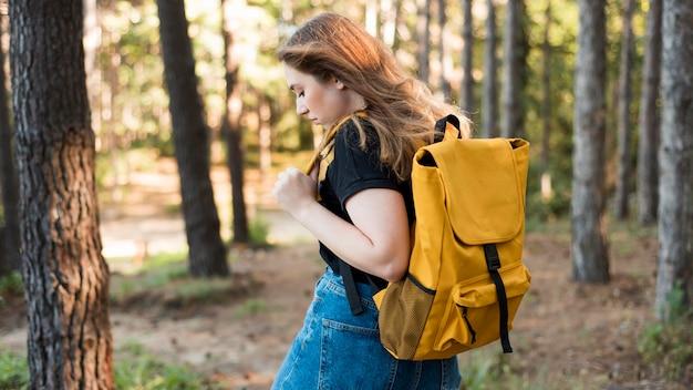 Donna a metà colpo con zaino nella foresta