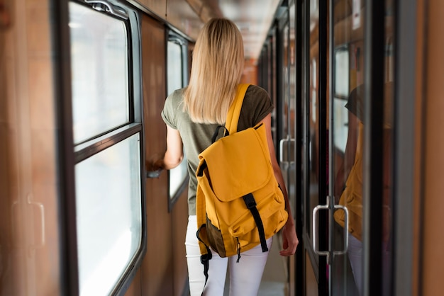 Mid shot woman with backpack in train