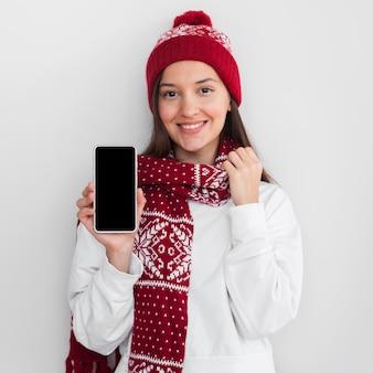 Середина выстрела женщина в шляпе, держащая телефон