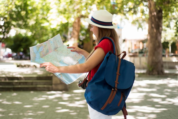 Mid shot woman with hat and map