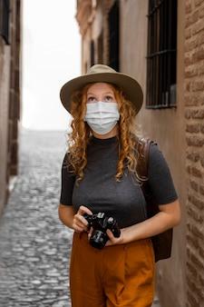 Donna a metà tiro con maschera e macchina fotografica