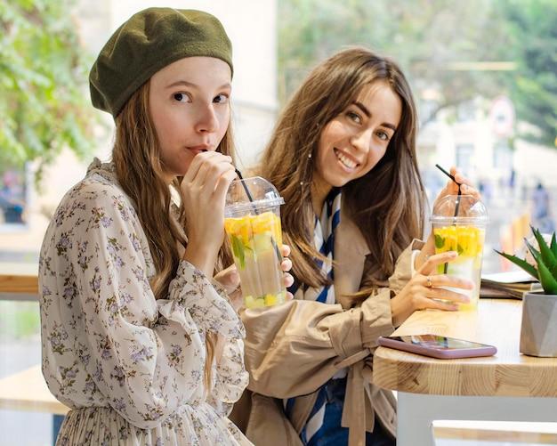 카페에서 신선한 음료를 마시는 중간 샷 여성