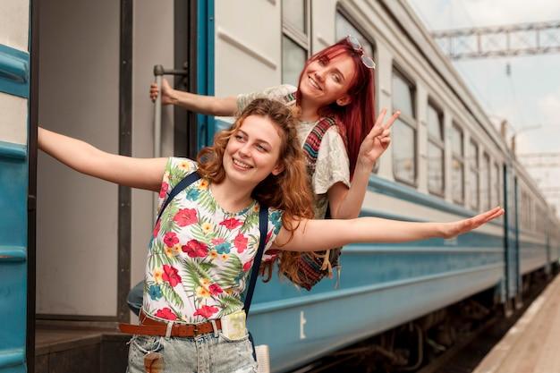 Женщины в середине кадра свисают с дверного проема поезда