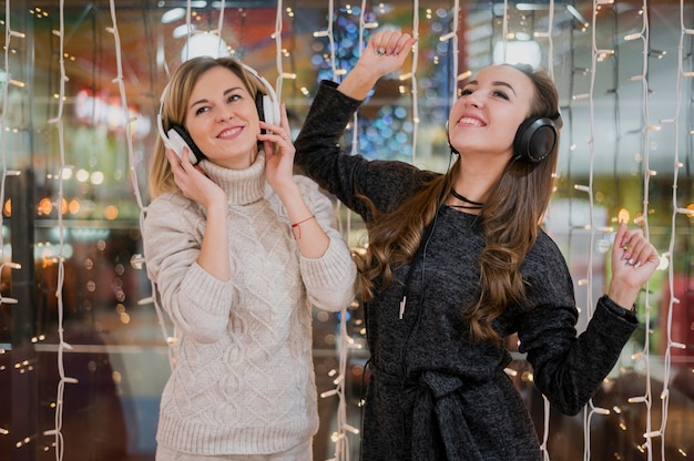 Mid shot women wearing headphones having fun around christmas lights