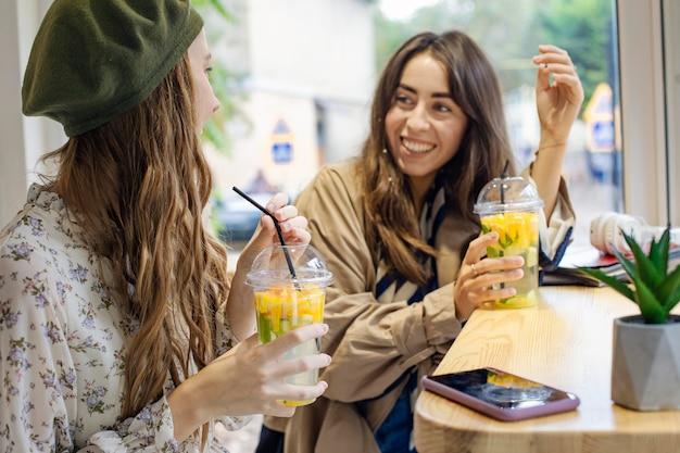카페에서 말하는 신선한 음료와 중간 샷 여자
