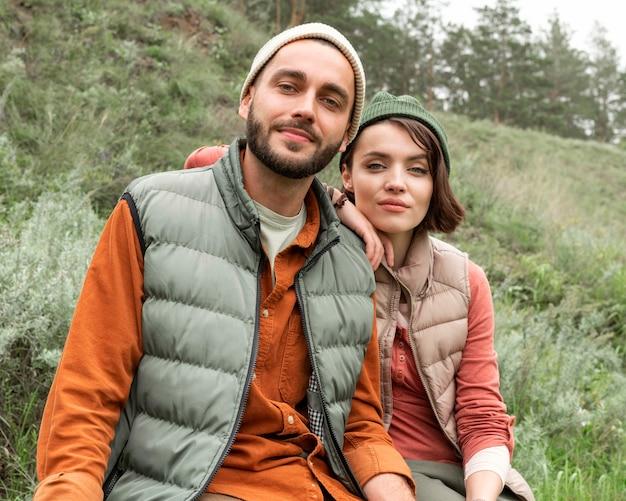 Середина выстрел молодая пара позирует на природе