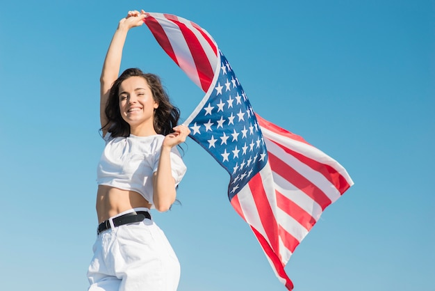 Mid shot young woman holding big usa flag and smiling