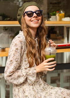 Mid shot young woman holding green smoothie