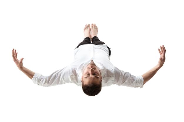 Студийный снимок midair beauty в полный рост привлекательного молодого человека, парящего в воздухе и не спускающего глаз