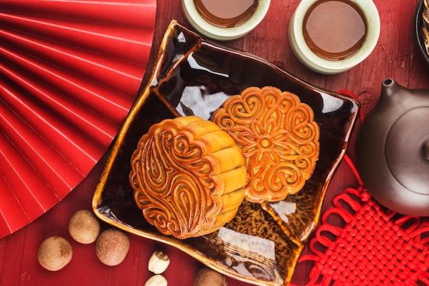 Концепция фестиваля midautumn традиционные лунные пирожные на столе с чашкой