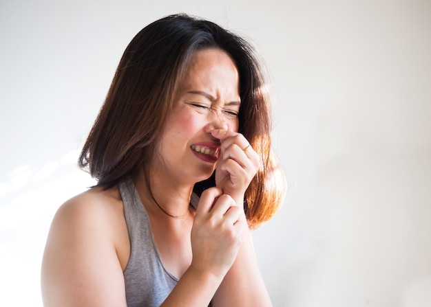 Middle adult asian woman sneezing and use hand squeezing nose