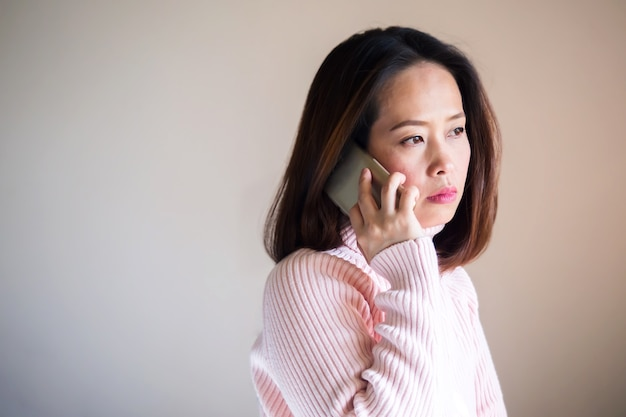 Middle adult asian woman using mobile phone