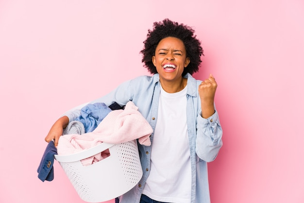 Middle age african american woman doing laundry isolated cheering carefree and excited. victory concept.