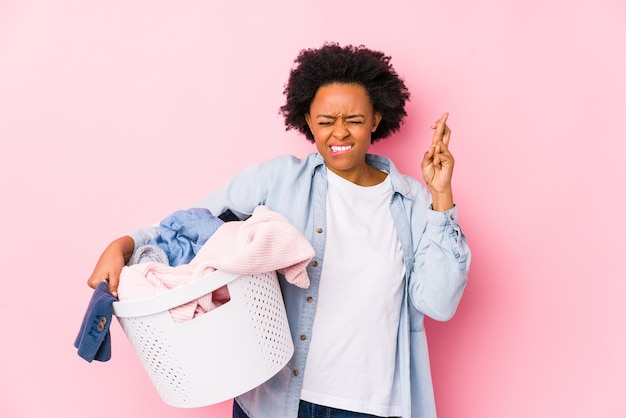 Middle age african american woman doing laundry isolated crossing fingers for having luck