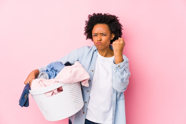 Middle age african american woman doing laundry isolated showing fist , aggressive facial expression.