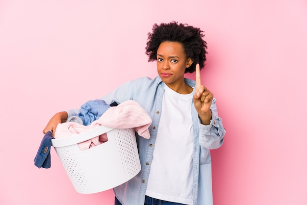 Middle age african american woman doing laundry isolated showing number one with finger.