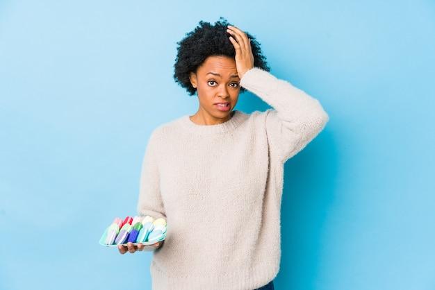 Афро-американская женщина среднего возраста ест миндальное печенье изолированно в шоке, она вспомнила важную встречу.