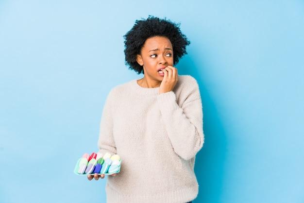 マカロンを食べる中年のアフリカ系アメリカ人の女性は、神経質で非常に不安な、噛む爪を孤立させました。