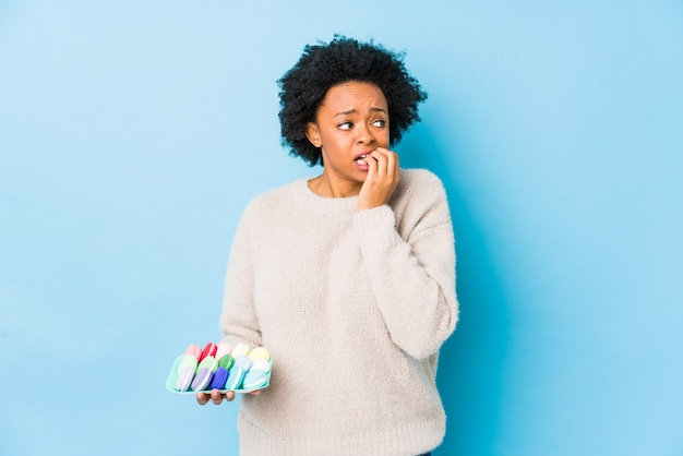 Middle age african american woman eating macaroons isolated biting fingernails, nervous and very anxious.