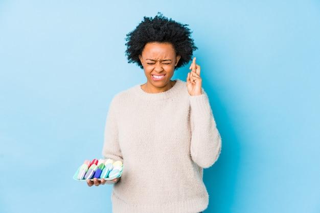 マカロンを食べる中年のアフリカ系アメリカ人女性は運を持っているために交差する指を分離しました