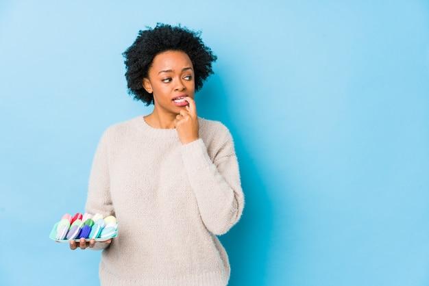 マカロンを食べる中年のアフリカ系アメリカ人女性は、コピースペースを見て何かについてリラックスした思考を分離しました。