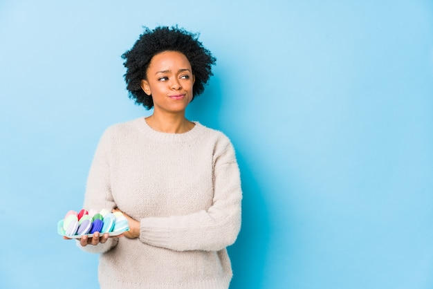Афро-американская женщина среднего возраста ест миндальное печенье изолированно, уверенно улыбаясь со скрещенными руками.