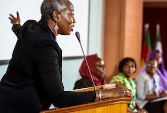 Женщина среднего возраста африканского происхождения, говорящая в микрофон