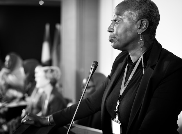 A middle age african descent woman speaking into a microphone