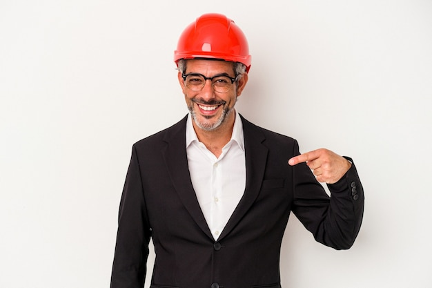 シャツのコピースペースを手で指している白い背景の人に分離された中年の建築家白人男性、誇りと自信を持って