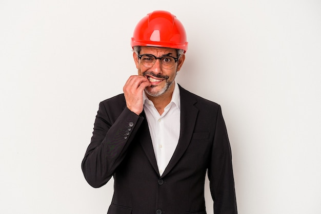 Middle age architect caucasian man isolated on white background  biting fingernails, nervous and very anxious.