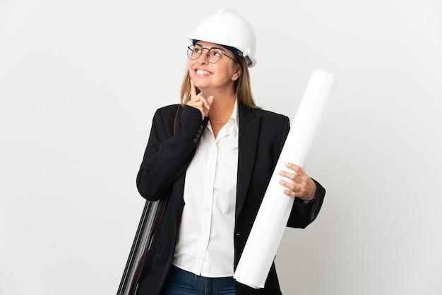 헬멧과 고립 된 청사진을 들고 중년 건축가 여자