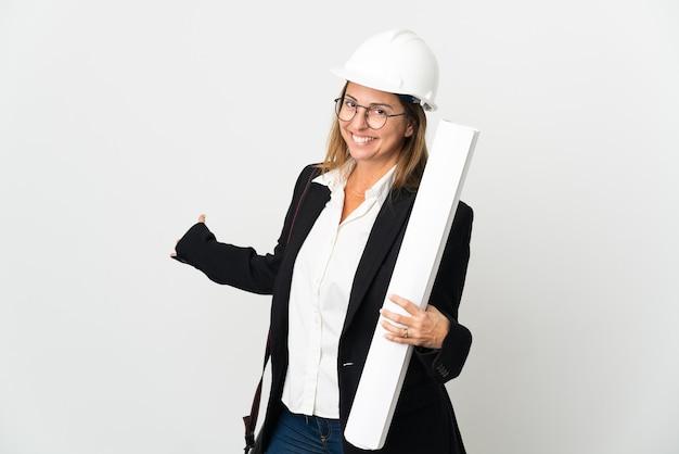 헬멧과 고립 된 배경 위에 청사진을 들고 중년 건축가 여자와 서 초대하기 위해 손을 옆으로 확장
