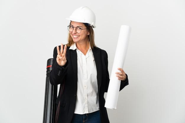 ヘルメットと孤立した背景の上に青写真を持って幸せな中年の建築家の女性と指で3を数える