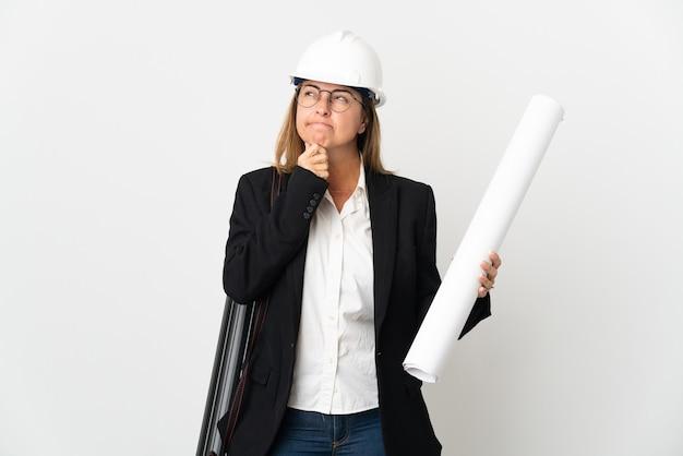 헬멧과 의심과 생각을 갖는 고립 된 배경 위에 청사진을 들고 중년 건축가 여자