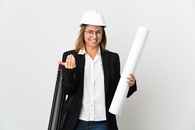 헬멧과 손으로와 서 초대 격리 된 배경 위에 청사진을 들고 중 년 건축가 여자. 와줘서 행복해