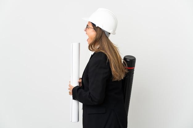 헬멧과 측면 위치에서 웃고 고립 된 배경 위에 청사진을 들고 중년 건축가 여자