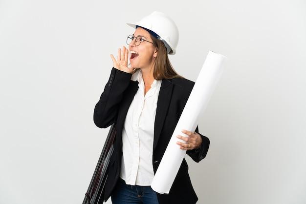 헬멧과 격리 된 배경 위에 청사진을 들고 중년 건축가 여자 입 벌리고 측면으로 외치는