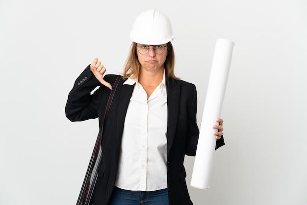 헬멧을 가진 중년 건축가 여자와 부정적인 표현으로 엄지 손가락을 보여주는 격리 된 배경 위에 청사진을 들고