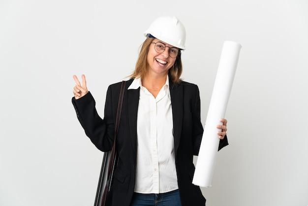 ヘルメットをかぶって、孤立した背景に青写真を持って笑顔と勝利のサインを示す中年の建築家の女性