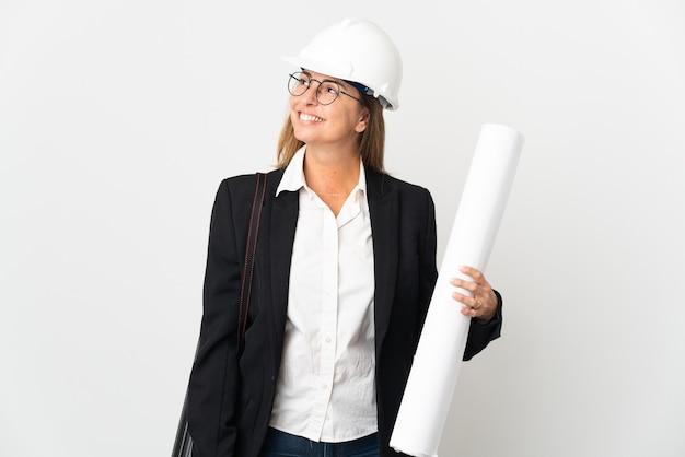 Женщина-архитектор среднего возраста в шлеме и держит чертежи на изолированном фоне, думая об идее, глядя вверх