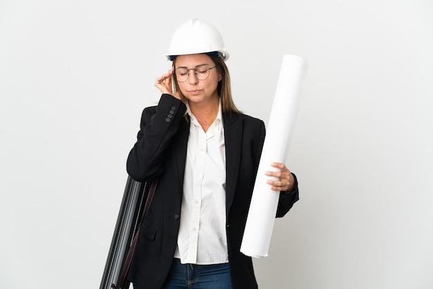 헬멧과 두통과 격리 된 배경 위에 청사진을 들고 중년 건축가 여자