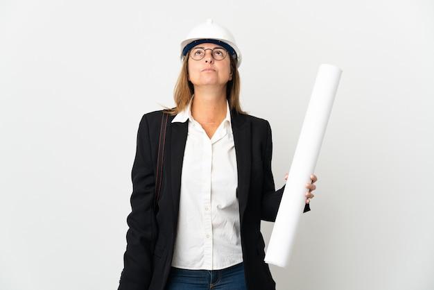 헬멧과 격리 된 벽에 청사진을 들고 찾고 중년 건축가 여자